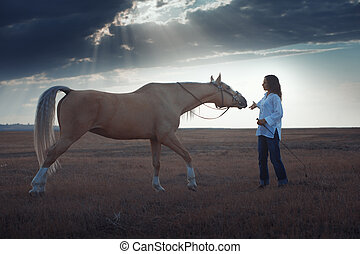 Woman and horse - Woman training horse in the steppe during...