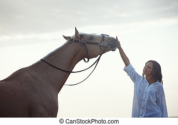 Woman and horse - Woman training horse outdoors during...