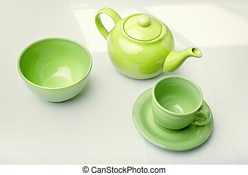 Tea service - Green teapot with cup and plate on a table