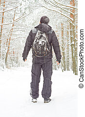 The man walking in winter forest