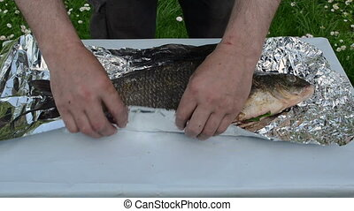 hand wrap fish foil bake - hands wrap big bream fish into...