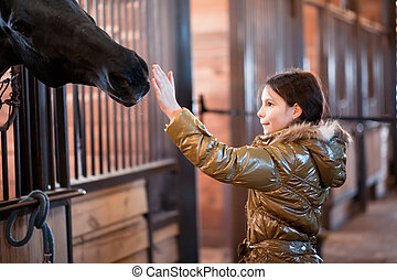 Girl stroking horse - Teenage girl stroking horse while it...