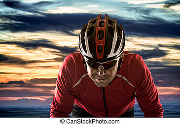 Cyclist with helmet against cloudy sunset sky.