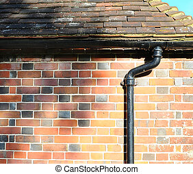 Drain pipe, roof tiles and bricks - Detail shot of an old...