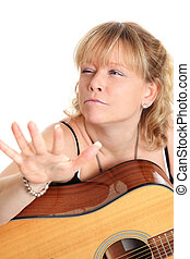 Female singer songwriter with an acoustic guitar White...