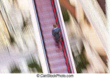 woman on a moving staircase in the shopping center