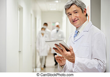 Doctor Holding Digital Tablet - Portrait of mature male...