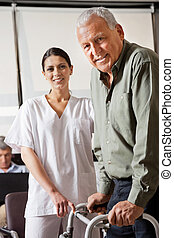 Nurse Helping Male Patient With Walker - Portrait of nurse...