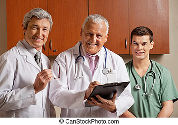 Happy Doctor With Colleagues - Portrait of happy senior male...
