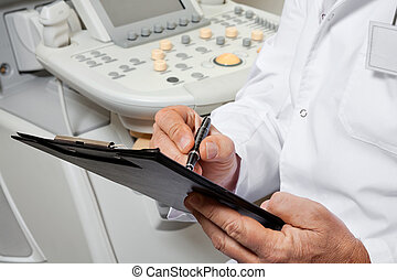 Male Doctor Writing On Clipboard - Midsection of male doctor...