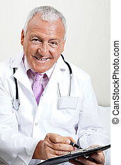 Doctor Writing On Clipboard - Portrait of senior male doctor...