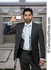 Man Holding Business Card - Handsome man holding up a...