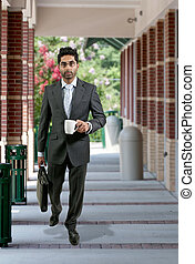 Man with Brief Case and Coffee - Handsome young man carrying...