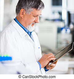Senior doctor/scientist using his tablet computer at work...