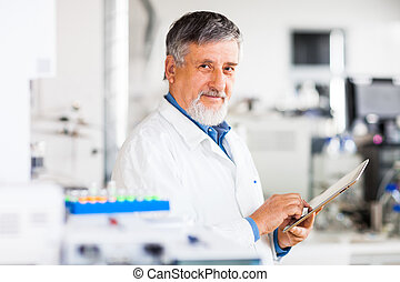 Senior doctor using his tablet computer at work (color toned...