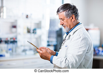 Senior doctor/scientist using his tablet computer at work