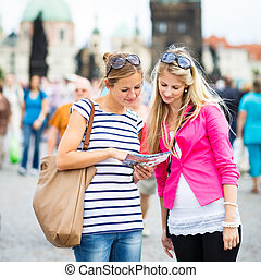 Two female tourists walking along the Charles Bridge while...