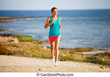 Young woman on her evening jog along the seacoast - Young...