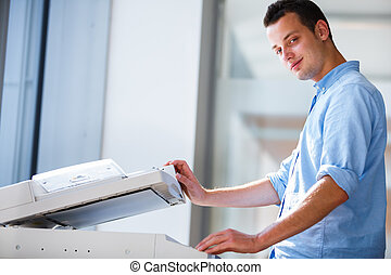 Handsome young man using a copy machine shallow DOF; color...