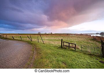 fence and dramatic sunrise