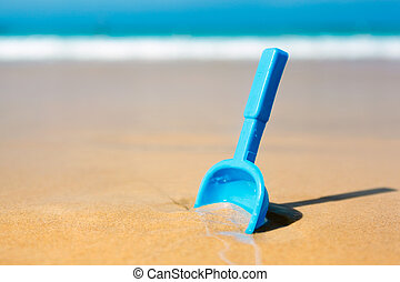 Small shovel in the sand on the beach - concept image