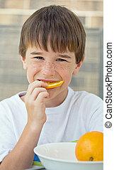 Boy Eating Orange Slice - Boy Eating An Orange Slice