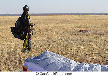 Paragliding - A male paraglider pilot right after landing