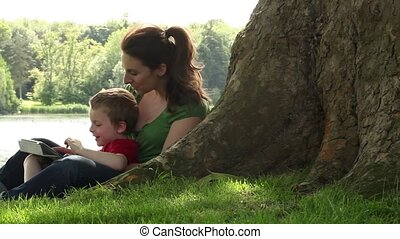 mum and son tablet in the park - mother reading from a...
