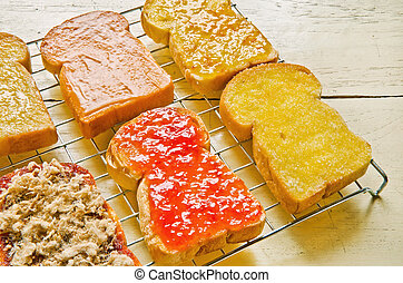 Several  toast with various topping on wood table