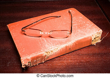 Book and eading Glasses - Reading glasses and a book full of...