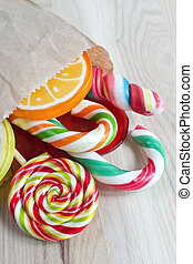 colorful lollipop in bag on wooden background