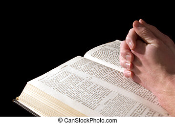 hands on Bible - A mans hands clasped in prayer over a Bible...