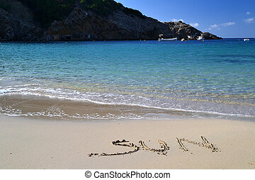 The word Sun written in the sand in Cala Vadella beach in...