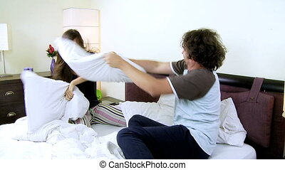Couple fighting with pillow happy