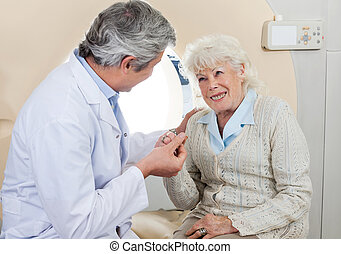 Doctor Comforting Senior Female Patient - Mature male doctor...