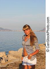 Young woman near rocky shore at sea - Beautiful girl walking...