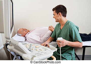 Radiologic Technician Smiling At Patient - Young male...