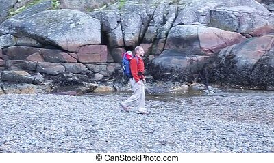 man walking with baby son on beach - a dad walking on the...