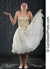 beautiful girl wearing in dress with corset stands in rain and catches drops by hand