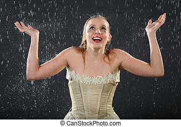 happy beautiful girl wearing in dress smiles in rain and catches drops by hands