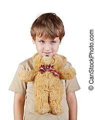 Close-up little boy in the beige t-shirt presses bear-toy by his chin to the chest.