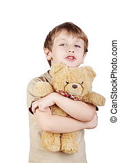 Boy in the beige t-shirt hugs bear-toy and says something, focus on bear