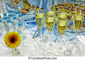 Wine, water, snacks and flower on a smorgasbord.