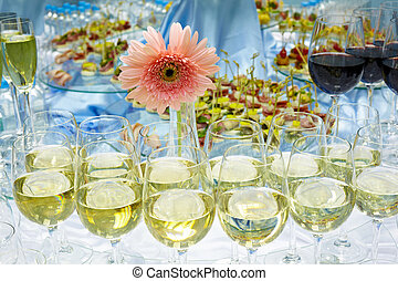 White and red wine in glasses, snacks, water and flower on a...
