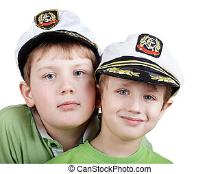 Two boys in green T-shirts and white sea peak-caps