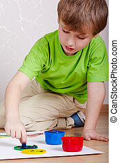 Little boy in the green t-shirt sits on the floor and plays with paints for drawing