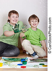 Two boys in green T-shirts sit on the floor with satisfied faces and show their right palms smeared with dirty-green paint, focus on right boy