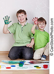 Two smiling boys in green T-shirts sit on the floor and show their right palms smeared with colour paints, focus on hands