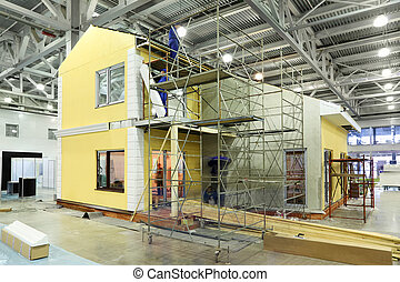 Team of builders build two-storey yellow cottage in large...