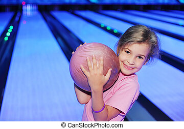 Smiling little girl dressed in pink T-shirt holds ball in...